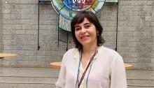Judit Camargo, fundadora de l'empresa de filtres solars intel·ligents Roka Furadada, somriu davant d'una paret de totxos grisos.